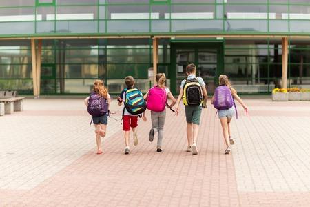 niños saliendo de la escuela: la educación primaria, la amistad, la infancia y las personas concepto - grupo de estudiantes de la escuela primaria felices con mochilas correr al aire libre Foto de archivo