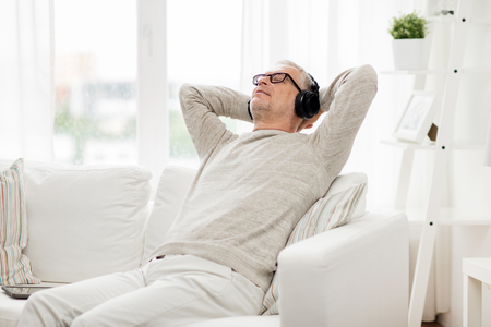 la tecnología, las personas y el concepto de estilo de vida - hombre mayor feliz en los auriculares escuchando música en casa