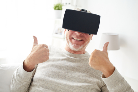 entertainment concept: 3d technology, augmented reality, gaming, entertainment and people concept - happy senior man with virtual headset or 3d glasses playing videogame at home