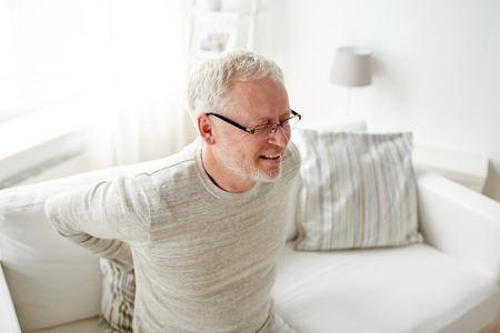 hurt: people, healthcare and problem concept - unhappy senior man suffering from pain in back or reins at home Stock Photo