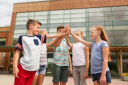 school yard: primary education, friendship, childhood and people concept - group of children or students making high five at school yard