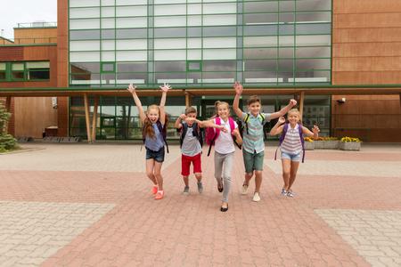 primair onderwijs, vriendschap, jeugd en mensen concept - groep van gelukkige basisschoolleerlingen met rugzakken hardlopen en wuivende handen buitenshuis