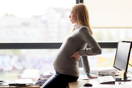 workplaces: pregnancy, business, work and people concept - pregnant businesswoman looking through window at office