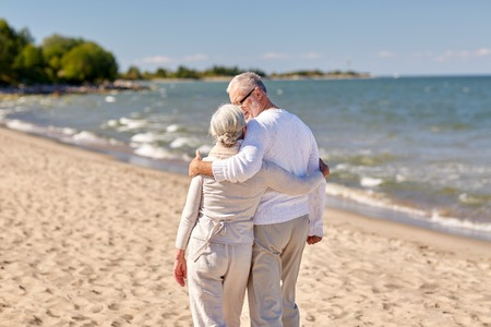 ancianos caminando: family, age, travel, tourism and people concept - happy senior couple hugging on summer beach