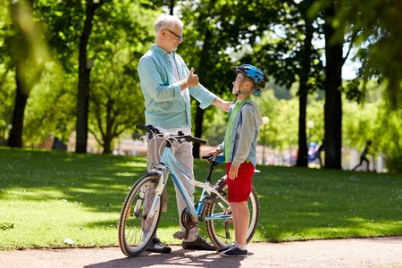 family, generation, safety and people concept - happy grandfather and boy with bicycle and bike helmet at summer park Stock Photo