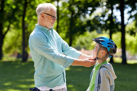 personas ayudando: familia, generación, la seguridad y el concepto de la gente - feliz abuelo al muchacho con el casco de bicicleta en el parque de verano Foto de archivo