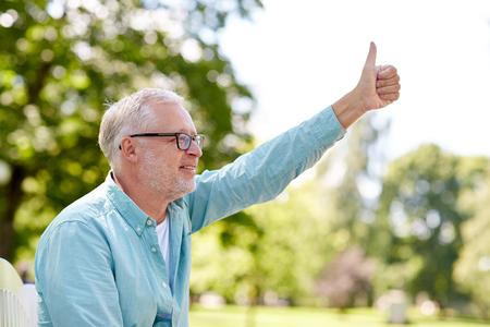 la vejez, el gesto y el concepto de la gente - hombre mayor feliz con gafas sentado en el parque de verano y que muestran los pulgares para arriba Foto de archivo