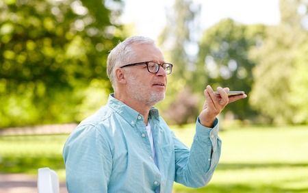 using voice: technology, senior people, lifestyle and communication concept - close up of happy old man using voice command recorder or calling on smartphone at summer park