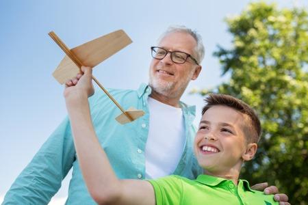 家族、世代、将来、夢と人コンセプト - 幸せな祖父と孫の青い空の上のおもちゃの飛行機で
