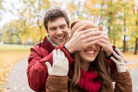 and guessing: love, relationships, season and people concept - happy young couple having fun in autumn park