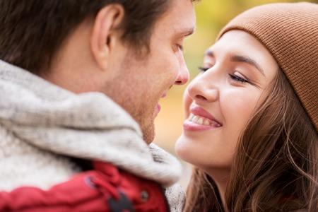 carita feliz: amor, las relaciones, la temporada y la gente concepto - cerca de la feliz pareja joven besos al aire libre