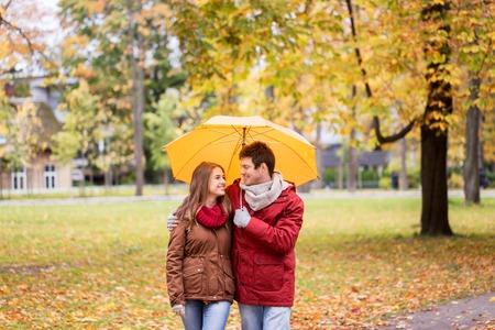 pareja abrazada: amor, las relaciones, la temporada, la familia y las personas concepto - feliz pareja con paraguas caminando en el parque del otoño Foto de archivo