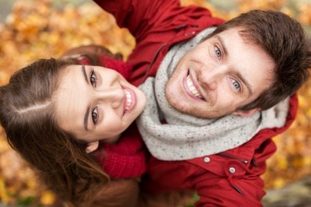 happy smiling: love, technology, relationship, family and people concept - close up of happy smiling young couple taking selfie in autumn park