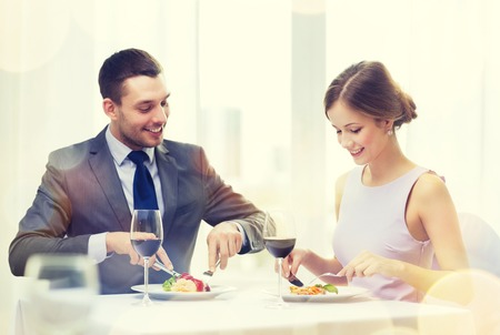 donna innamorata: ristorante, coppia e concetto di vacanza - coppia sorridente mangiare piatto principale con vino rosso al ristorante Archivio Fotografico
