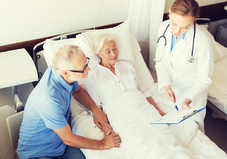 health care and medicine: medicine, age, health care and people concept - senior woman, man and doctor with clipboard at hospital ward Stock Photo