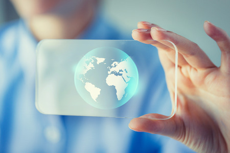 body parts cell phone: business, technology, international communication, mass media and people concept - close up of woman hand holding and showing transparent smartphone with globe on screen