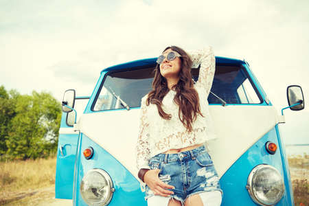 young women: summer holidays, road trip, vacation, travel and people concept - smiling young hippie women in minivan car Stock Photo