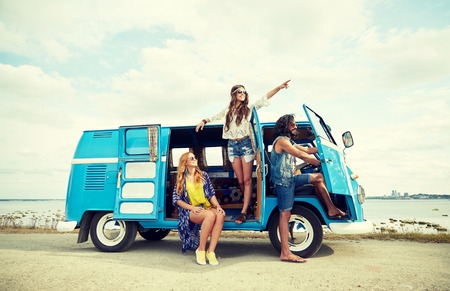 summer holidays, road trip, vacation, travel and people concept - smiling young hippie friends in minivan car on beach Foto de archivo
