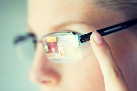 business, media, future technology, information and people concept - close up of woman in eyeglasses with virtual screen projection pointing finger to earpiece