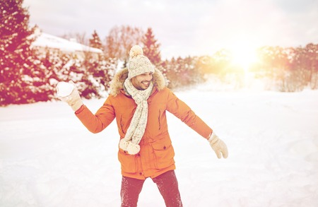 palle di neve: people, season and leisure concept - happy young man playing snowballs in winter