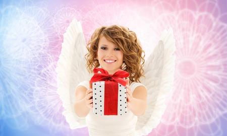 angel birthday: people, holidays and birthday concept - happy young woman with angel wings holding gift box over rose quartz and serenity pattern background