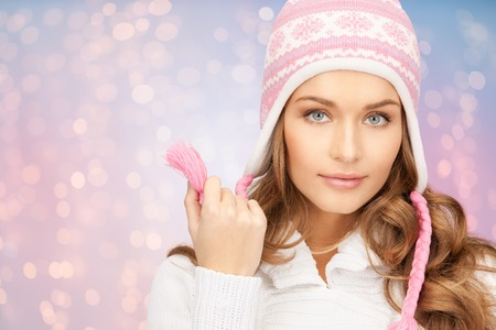 winter holidays, christmas and people concept - close up of young woman in hat and scarf over rose quartz and serenity lights background Stock Photo