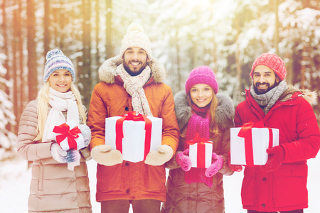 holidays, christmas, season, friendship and people concept - group of smiling friends with gift boxes in winter forest Stock Photo