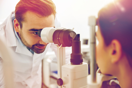 tonometer: health care, medicine, people, eyesight and technology concept - optometrist with non contact tonometer checking patient intraocular pressure at eye clinic or optics store Stock Photo