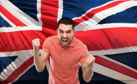 englishman: emotion, aggression, patriotism, gesture and people concept - angry young man showing fists and shouting over brittish flag