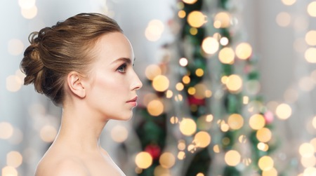 health, people, holidays and beauty concept - beautiful young woman face over christmas tree lights background Stock Photo