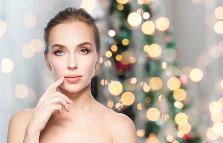 plastic christmas tree: beauty, people, holidays and plastic surgery concept - beautiful young woman showing her lips over christmas tree lights background