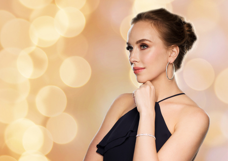 people, luxury, jewelry and fashion concept - beautiful woman in black wearing diamond earrings and bracelet over holidays lights background Stock Photo