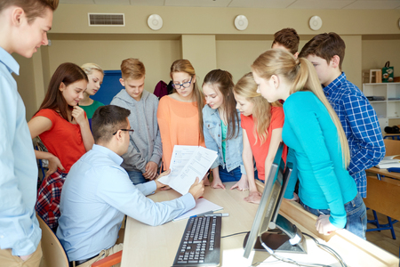 school classroom: education, school, learning, teaching and people concept - group of students and teacher talking in classroom