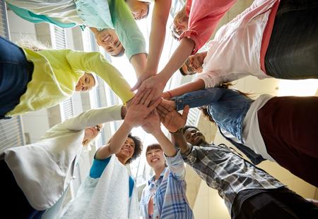 教育、学校、チームワーク、人々 のコンセプト - テーブルの上の互いの上に手で留学生のグループ