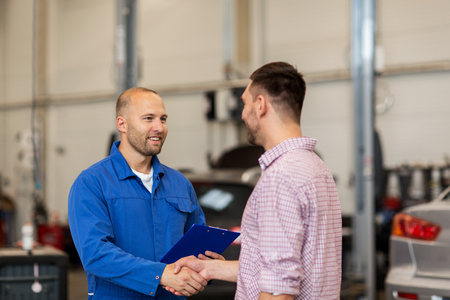 auto-service, reparatie, onderhoud, gebaar en mensen concept - monteur met klembord en man of eigenaar schudden handen bij de auto winkel Stockfoto