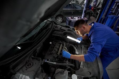 車のサービス、修理、保守および人々 のコンセプト - ランプをワーク ショップで働くオート メカニック マニュアル