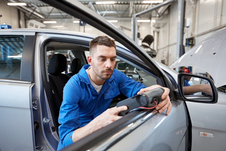 automobiles: service, repair, maintenance and people concept - mechanic man with automotive diagnostic scanner checking car system at workshop Stock Photo
