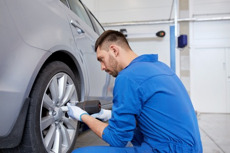 car service, repair, maintenance and people concept - auto mechanic man with electric screwdriver changing tire at workshop 版權商用圖片