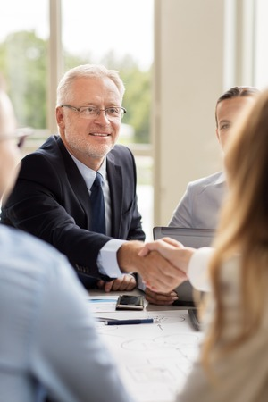 businesspeople: business, people, gesture, cooperation and partnership concept - smiling senior businessman making handshake with woman at office Stock Photo
