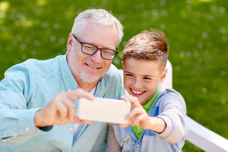 family, generation, technology and people concept - happy grandfather and grandson with smartphone taking selfie at summer park Фото со стока