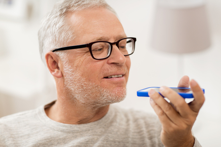 using voice: technology, people, lifestyle and communication concept - close up of happy senior man using voice command recorder or calling on smartphone at home