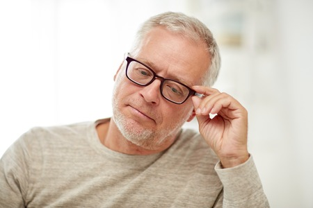 unhappy man: old age, problem and people concept - close up of senior man in glasses thinking Stock Photo