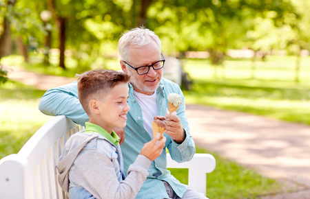 family, generation, communication and people concept - happy grandfather and grandson eating ice cream at summer park Stock Photo