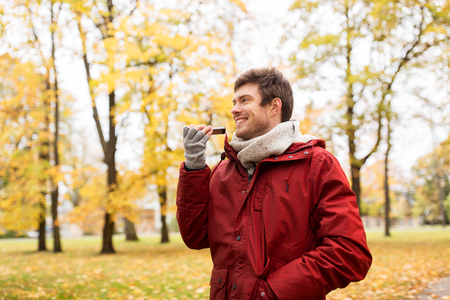 using voice: leisure, technology, communication and people concept - smiling hipster man using voice command recorder or calling on smartphone at autumn park