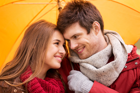 pareja abrazada: love, relationship, season, family and people concept - happy couple with umbrella walking in autumn park Foto de archivo