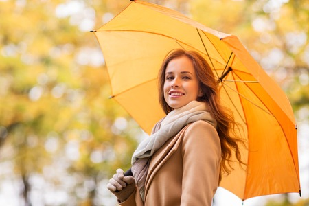 beautiful weather: season, weather and people concept - beautiful happy young woman with yellow umbrella walking in autumn park Stock Photo
