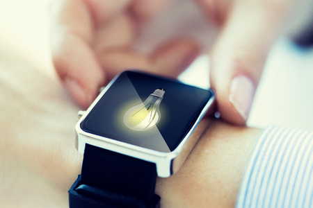 conection: business, technology, communication, conection and people concept - close up of woman hands with lightbulb icon on smartwatch screen Stock Photo
