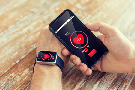 technology, health care, application and people concept - close up of male hand holding smart phone and wearing smart watch with red heart icon on screen and measuring pulse