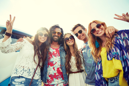 summer holidays, road trip, vacation, travel and people concept - smiling young hippie friends over minivan car showing peace hand sign Stock Photo