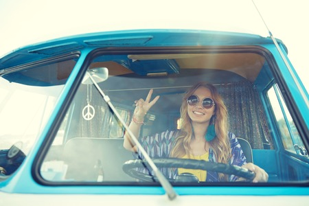 mujer hippie: summer holidays, road trip, vacation, travel and people concept - smiling young hippie woman driving minivan car and showing peace gesture